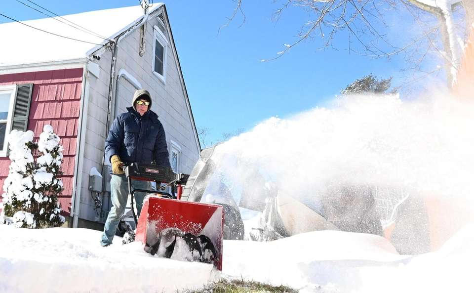 Barry Hill, uses a snowblower to clear snow