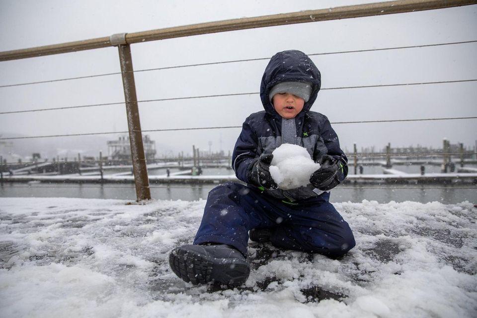 Matthew Bergold, 3, makes a snowball in Port