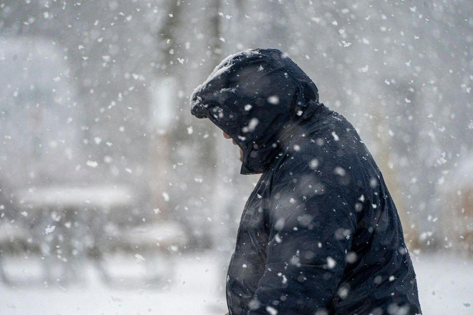 A man walks in the snow in Greenport