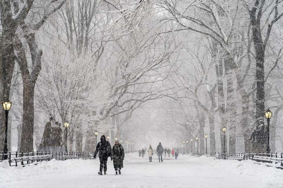 People walk in Central Park on a snowy