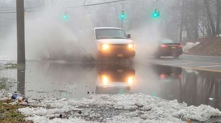 Vehicles drive through puddles of rain and melting
