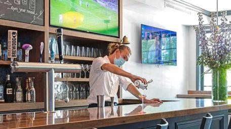 A masked bartender mixes a cocktail at Main