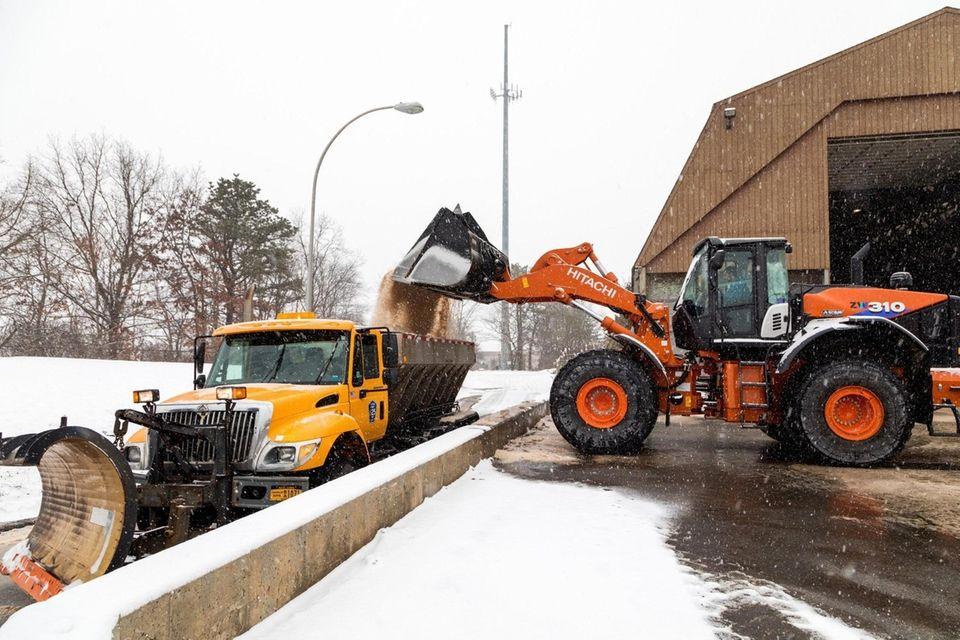 A front-end loader fills a plow with salt