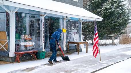 A man shovels snow in front of the