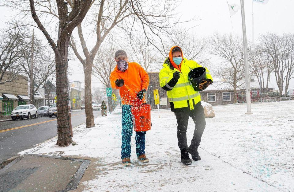 Greenport Village employees salt the sidewalk on Front
