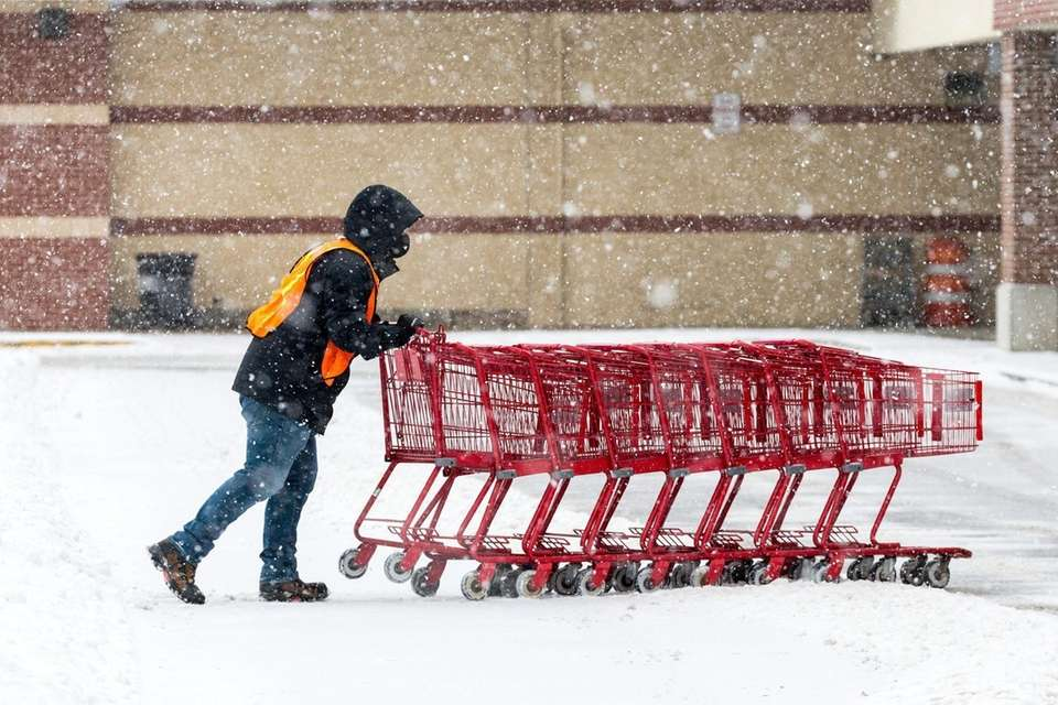 An employee retrieves shopping carts in the snow