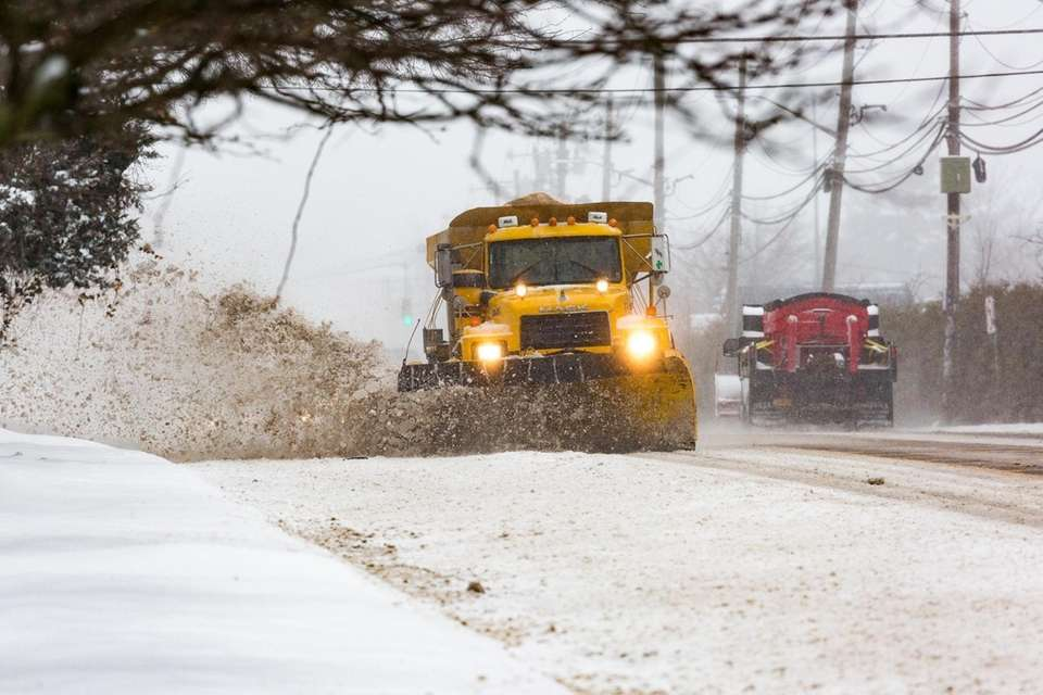A plow clears eastbound lanes of Jericho Turnpike