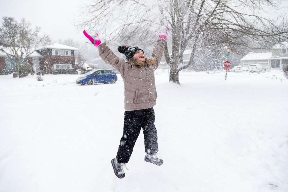 Amelia Elia, 8, tosses snow into the air