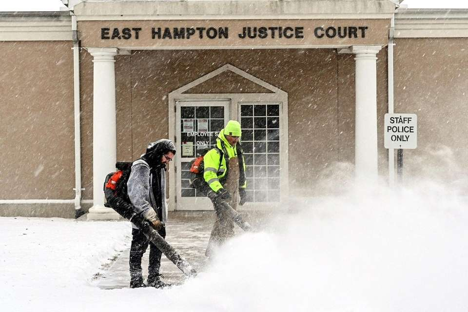 East Hampton Town employees clear the sidewalk at