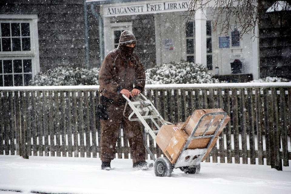 A UPS driver delivers packages during a snowstorm