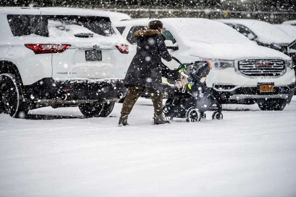 A woman pushes a stroller during today's snowstorm