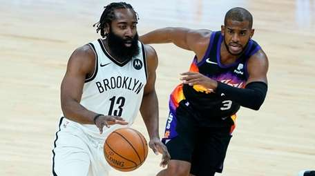 Nets guard James Harden drives as Suns guard