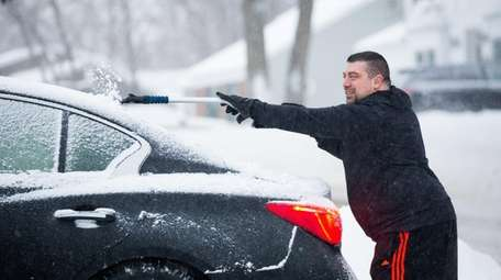 Chris Voccola clears ice and snow from his