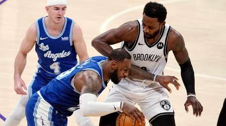 Lakers forward LeBron James, center, is defended by
