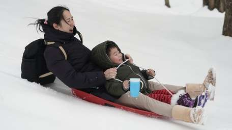 Zachary Gu, 3, sleds with his mom Cristy