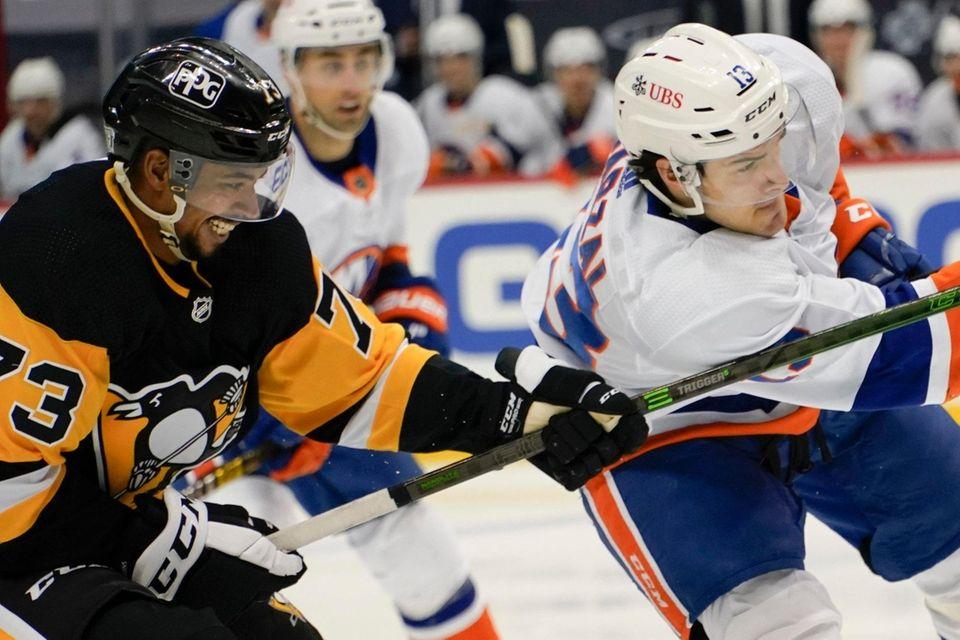 The Pittsburgh Penguins' Pierre-Olivier Joseph (73) checks the