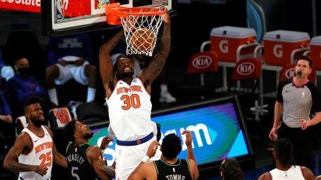 The Knicks' Julius Randle, center, dunks as Malik