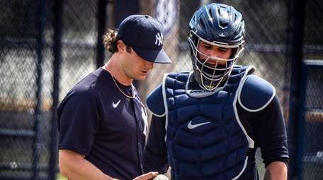 Gerrit Cole talks with catcher Gary Sanchez after