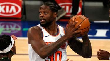 Julius Randle, center, of the Knicks looks to