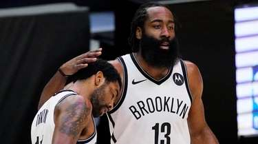 Nets guard Kyrie Irving, left, gets a pat