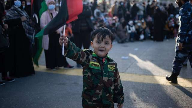 A child in fatigues waves a Libyan flag