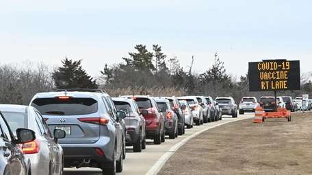 Vehicles line up at a COVID-19 vaccine site