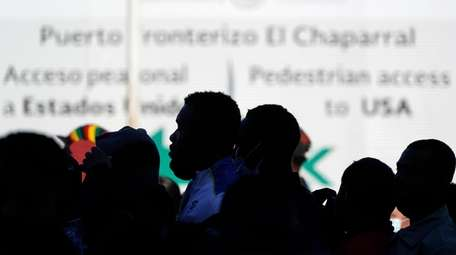 Asylum seekers waiting in Mexico stand in line