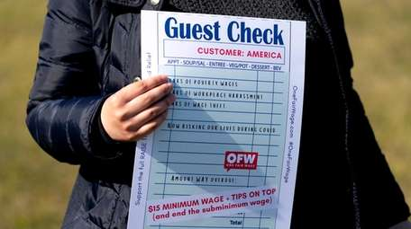 A woman holds a mock guest check during