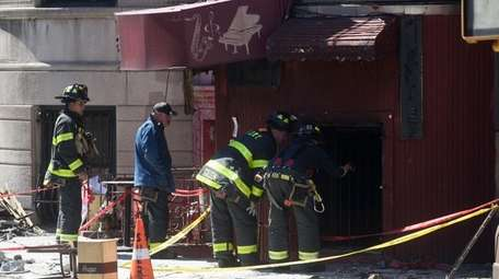 FDNY firefighters look into the ground floor of