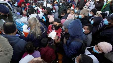Asylum-seekers receive food as they wait for news