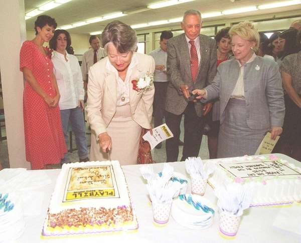 Lillian Barbash cuts a cake in the shape