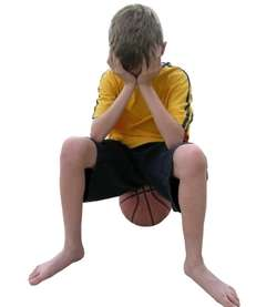 A boy sitting on a ball looking sad.