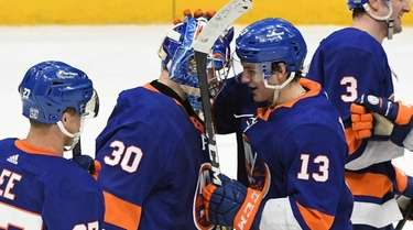 Islanders teammates congratulate goaltender Ilya Sorokin on the
