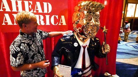 Sculptor Tommy Zegan wipes fingerprints from his golden