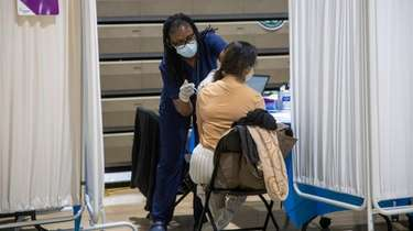 A woman gets vaccinated at Elmont Memorial High