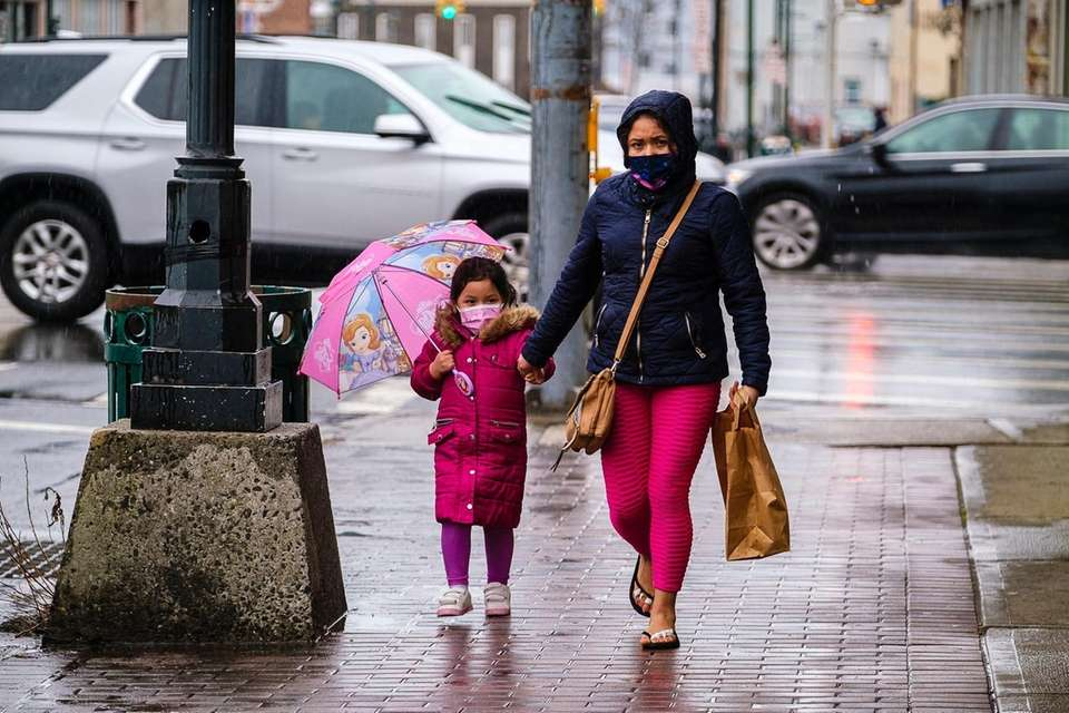 A woman and her daughter stroll hand in