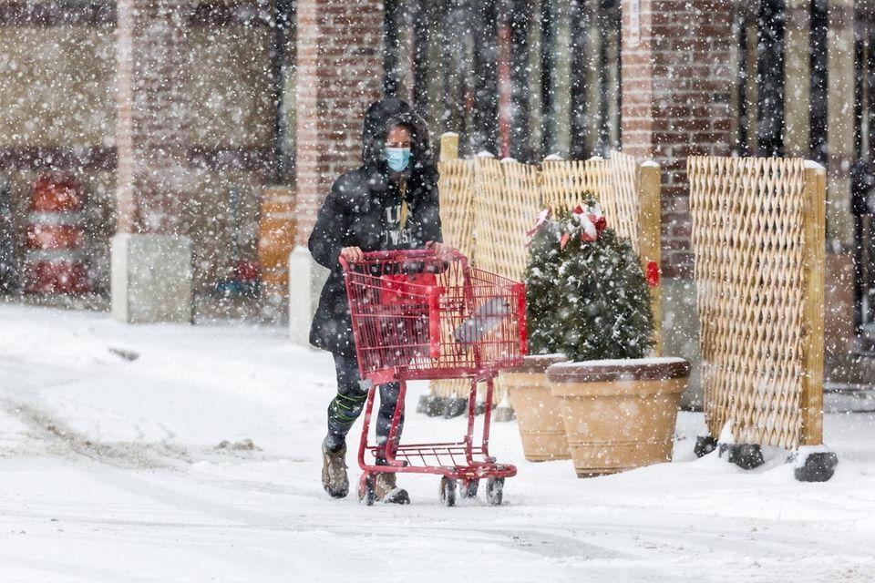 A woman pushes a shopping cart through the