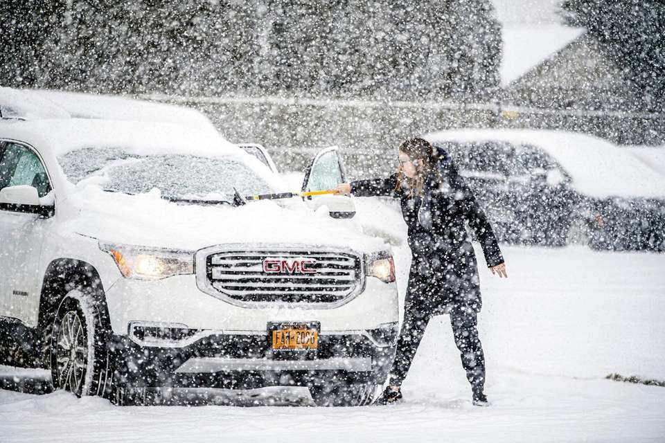 A woman cleans her car during today's snowstorm