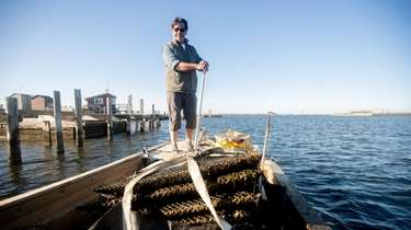Chuck Westfall of Thatch Island Oysters stands on