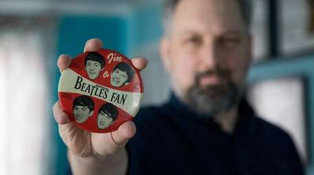 Ron Seifried holds a Beatles fan pin.