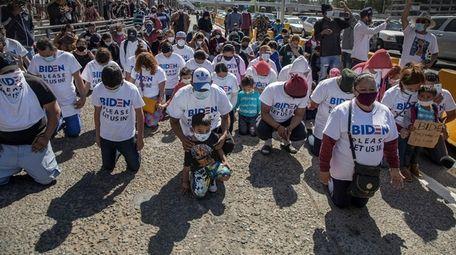"Migrants wearing T-shirts that read ""Biden please let"