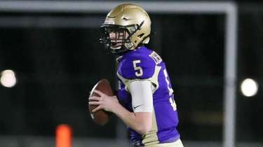 Sayville's Jack Cheshire (5) drops back to pass