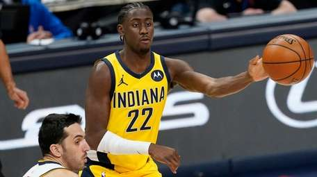 Pacers guard Caris LeVert, back, passes the ball