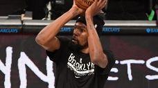 Nets forward Kevin Durant shoots before an NBA