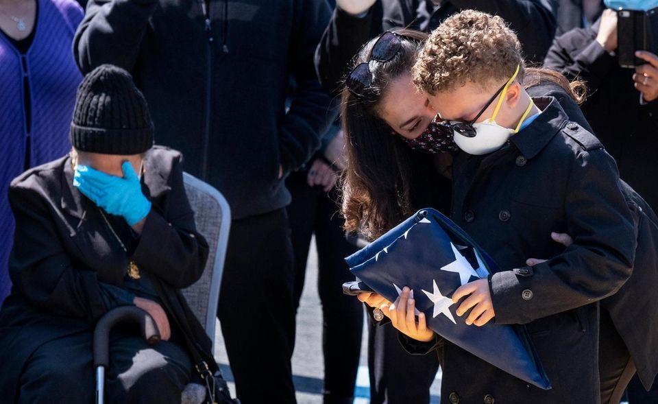 Robert Cardona Jr., 9, holds the flag that