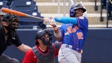 Mets' Francisco Lindor (12) follows through on a