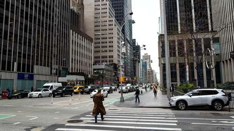 Pedestrians walk along Sixth Avenue on Wednesday, where