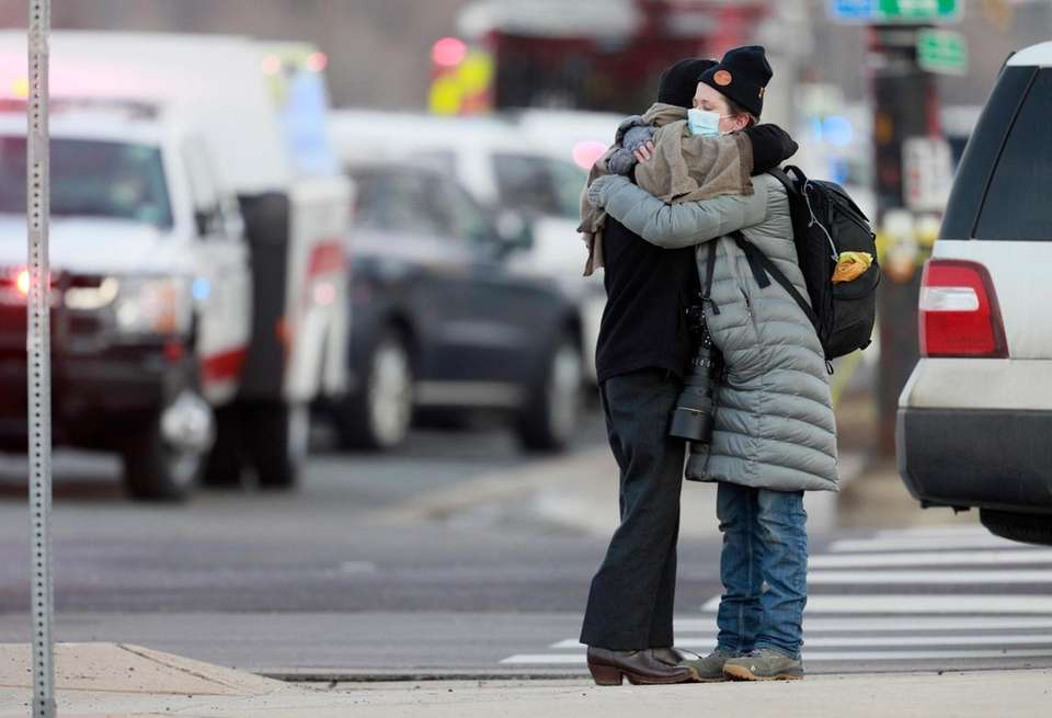 Women hug on the corner of Broadway and