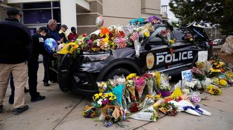 People leave flowers on a Boulder, Colo., police