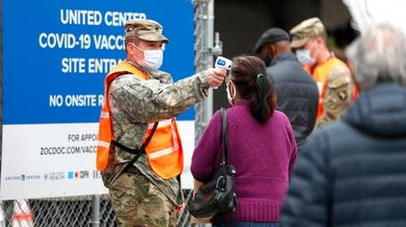A National Guard member checks the temperature of